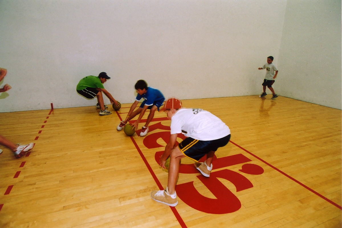 Boys playing dodgeball in racquetball court at Red's in Lafayette, LA.
