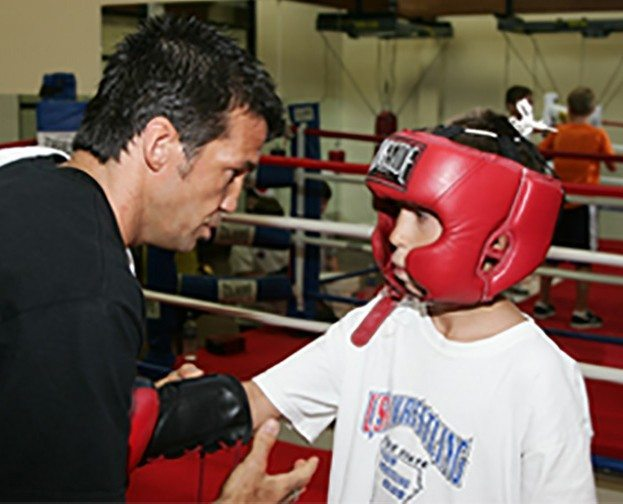 Chad Broussard, boxing personal trainer, coaching young boy in boxing ring at Red's in Lafayette, LA.