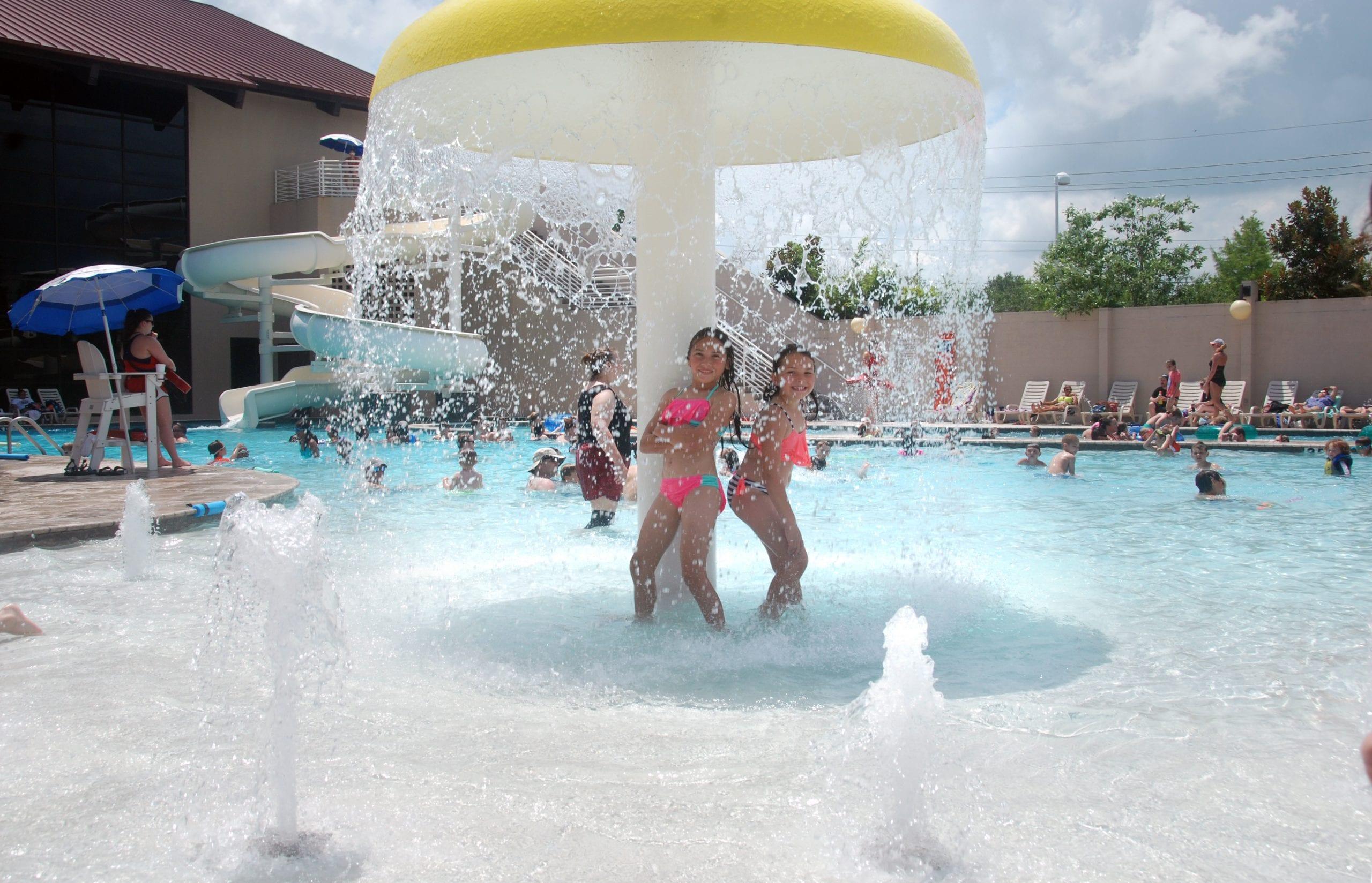 Jaelyn and Kamryn Benham under mushroom in kids pool at Red's in Lafayette, La