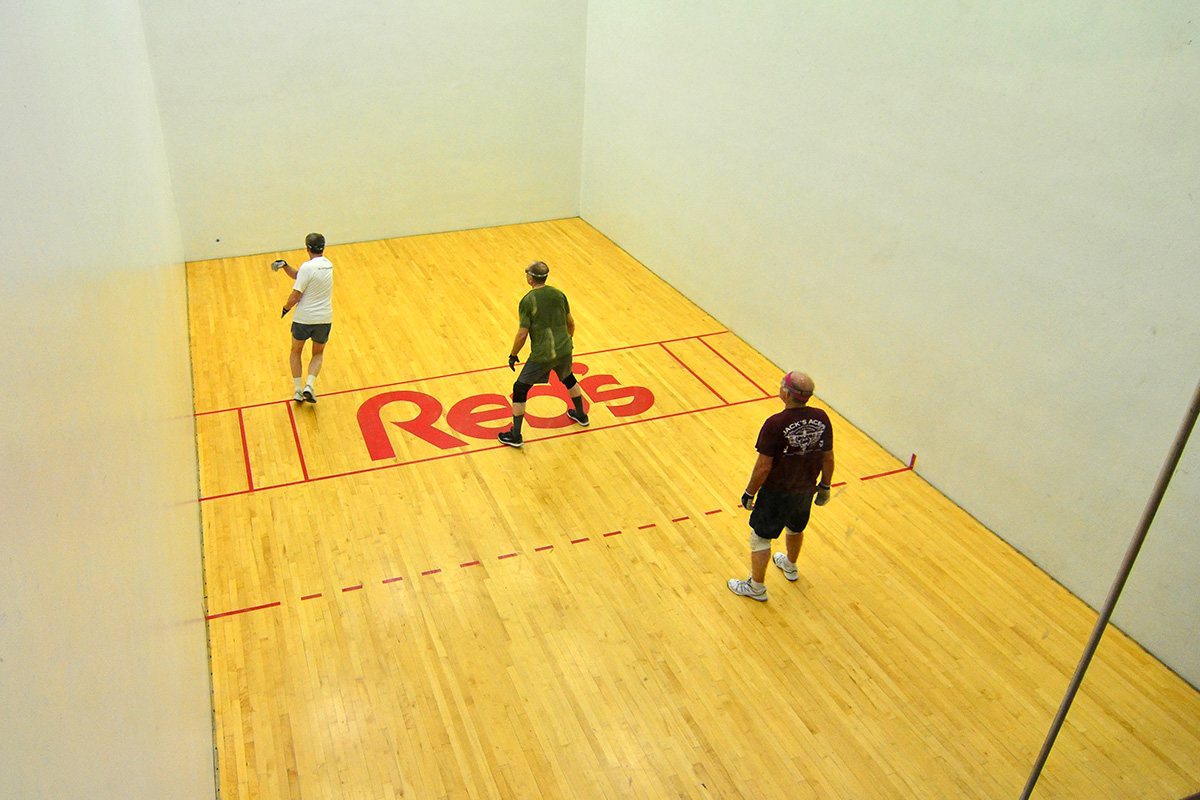Three men playing handball on Red's racquetball court in Lafayette, LA.