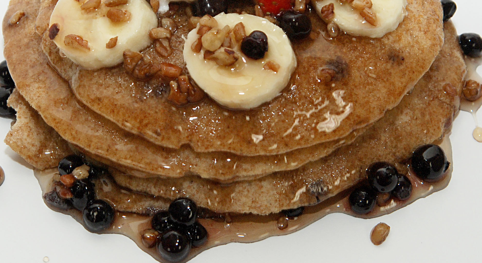 Whole wheat pancakes with bananas, blueberries and pecans dripping with syrup.